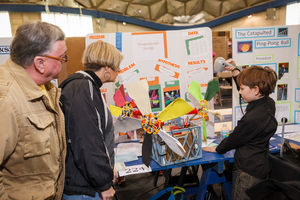 A few adults examine a display and receive an explanation form a young student.